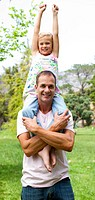Joyful father giving his daughter piggy_back ride in a park