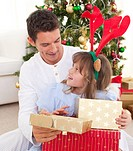Portrait of a smiling father and his daughter opening Christmas presents in the living_room