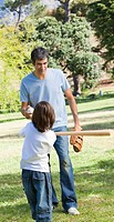 Father and his son playing baseball in a park