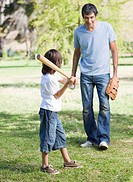 Cute little boy playing baseball with his father in the park