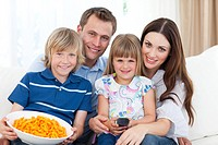Portrait of a smiling family eating crisps while watching TV in the living room