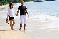 Young woman holding hand of a mid adult man and walking on the beach