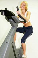 Young woman in Fitness Studio training on bike simulator Spinning