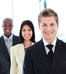 Smiling businessman in front of his team in office