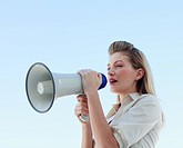 Blonde businesswoman shouting through megaphone outdoors