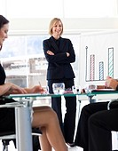 Attractive mature businesswoman smiling at her colleagues in a meeting