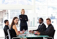 Serious businesswoman looking at the camera in a meeting with her team