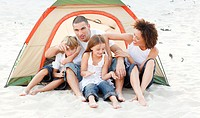 Happy young family camping on beach