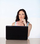 Young woman working with her laptop looking at the camera