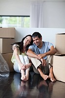 Happy lovers moving house with boxes
