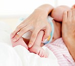 Patient´s hands holding a newborn baby in bed in hospital