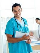 Attractive male doctor holding a medical clipboard in a hospital