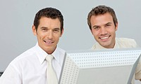 Smiling businessmen working together at a computer in the office