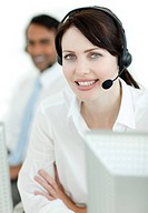 Female customer service agent at work with her colleague in the background