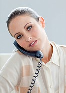 Serious businesswoman talking on phone in the office