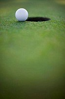 Close_up of a golf ball near a hole