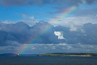 Rainbow over Godrevy lighthouse with blue sea and white clouds in summer sky above the ocean taken from St Ives Cornwall Southwest England UK United K...