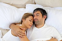 Caring lovers sleeping lying in the bed at home