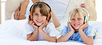 Close_up of siblings listening music with headphones