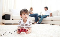 Cute little boy playing video games lying on the floor