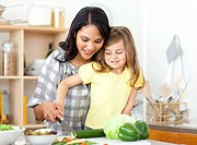 Blond child cutting vegetables with her mother in the kitchen