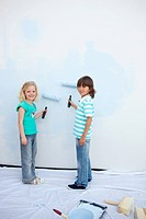 Cute siblings painting a wall in their new house