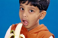 Boy eating banana holding in hand MR152