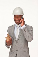 Attractive ethnic architect on phone holding plans against white background