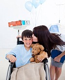 Cheerful smiling little boy sitting on wheelchair and his mother at the hospital