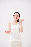 Young woman doing exercise, using dumbbells, white background