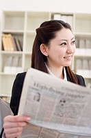 Young woman reading newspaper in office, smiling