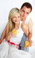 Young couple drinking orange juice in bed