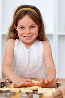 Smiling beautiful little girl baking in the kitchen
