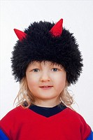 portrait of a cute boy with cap with horns isolated on white