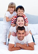 Happy young parents and children playing in bed together