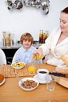 Boy having breakfast with his mother in kitchen