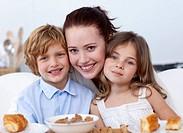 Children having breakfast in kitchen with their mother