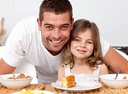 Portrait of father and daughter having breakfast in kitchen