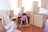 Nice kid playing with boxes in new house