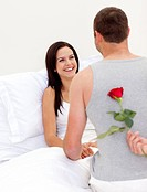 Husband surprising his beautiful wife with a rose in bed