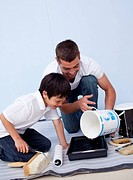 Man and little boy painting a bedroom together at home