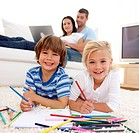 Smiling brother and sister painting on floor in living_room