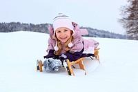 Kleines Mädchen auf Schlitten im Schee, Schweiz