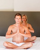Young couple doing yoga on bed together