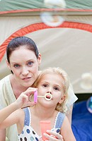 Mother and daughter blowing bubbles in tent