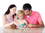 Parents helping their daughter doing homework at home