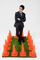 businessman surrounded by traffic cones
