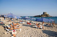 People sunbathing at Kefalos beach, Kastri island with chapel St. Nicholas in background, Kefalos, Kos, Greece