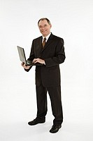 A caucasian businessman with a receding hairline wearing a black business suit and white shirt  He is shown on a white background holding a laptop and...