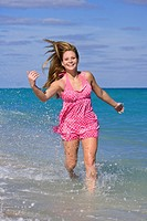Beautiful Caucasian female teenage running through to surf wearing a colorful bikini